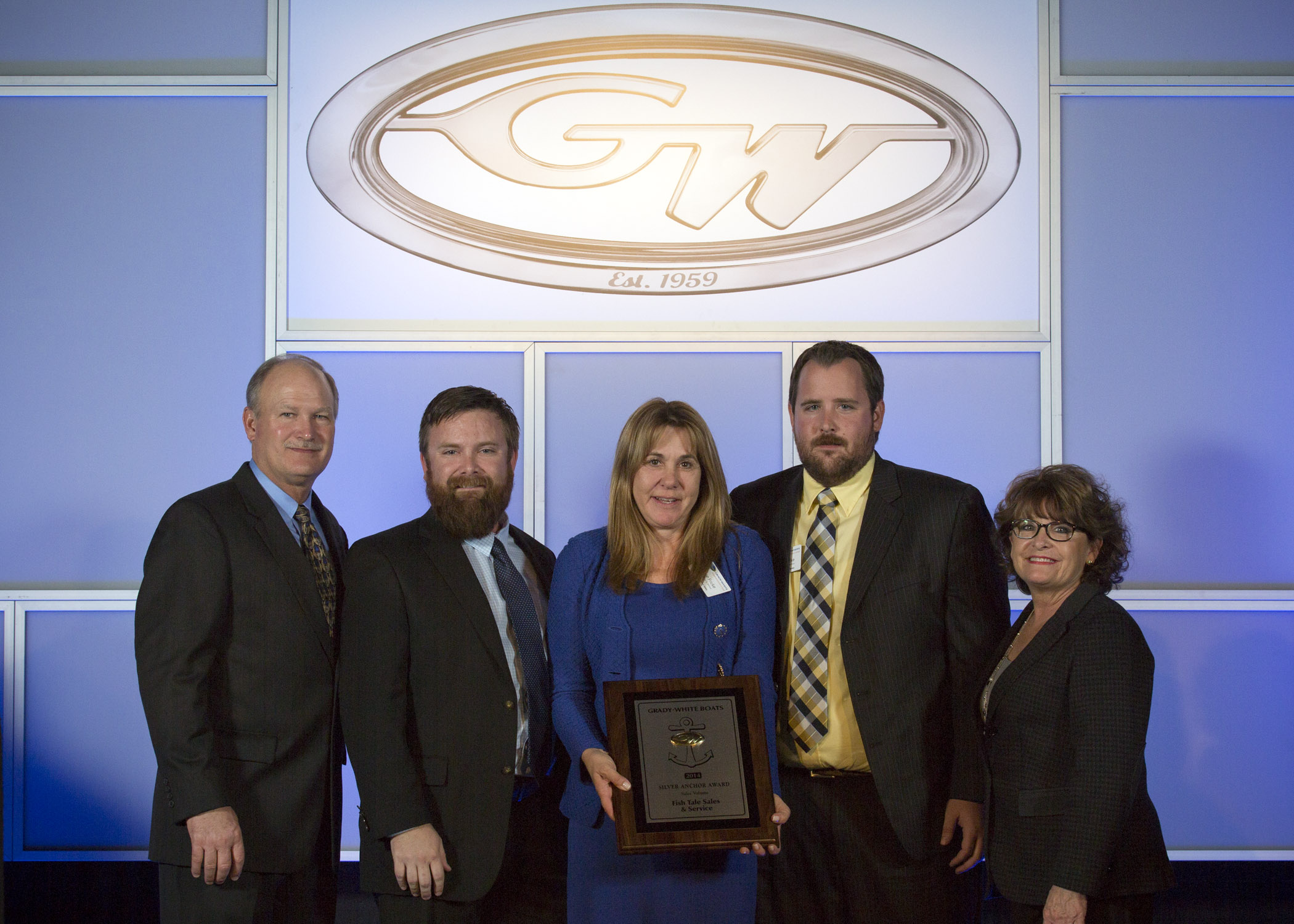 Joey Weller, vice president of sales for Grady-White Boats, left, and Kris Carroll, president of Grady-White Boats, right, present the coveted Gold Anchor Award for Outstanding Customer Satisfaction to Diane Fricke, Travis Fricke and Justin Fricke with Fish Tale Sales & Service of Fort Myers Beach.